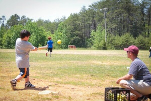 A camper hits a softball out into the field.