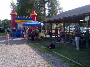 Shoppers enjoying a moon bounce and bluegrass music at the farmers' market.