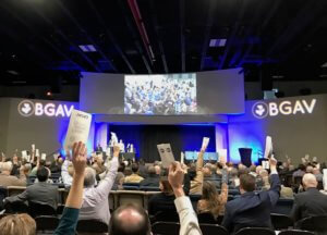 Messengers raise their ballots to vote during the Wednesday morning business session.